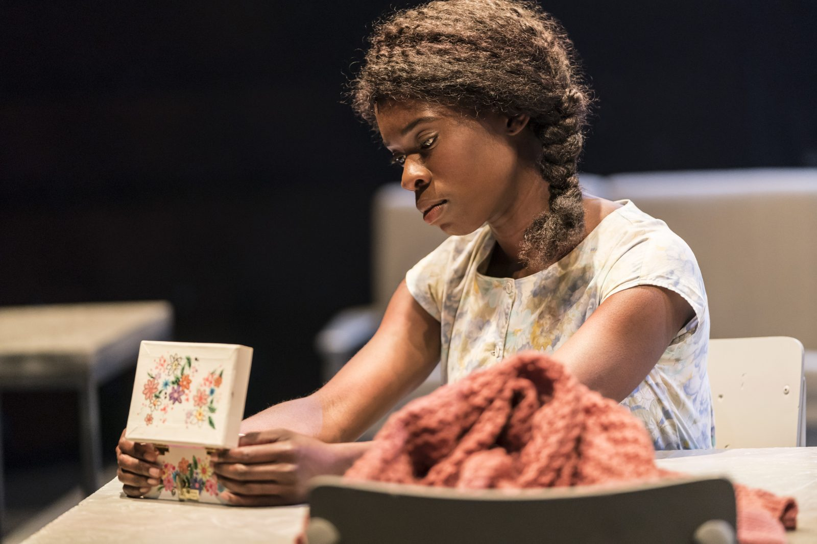 faith omole as joy, sat at table looking down into a musical box