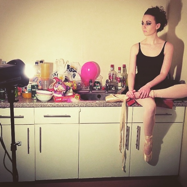 pippa at photoshoot in black ballet wear and pointe shoes with heavy make-up, sat on a counter and looking at camera taking a photo out of the shot