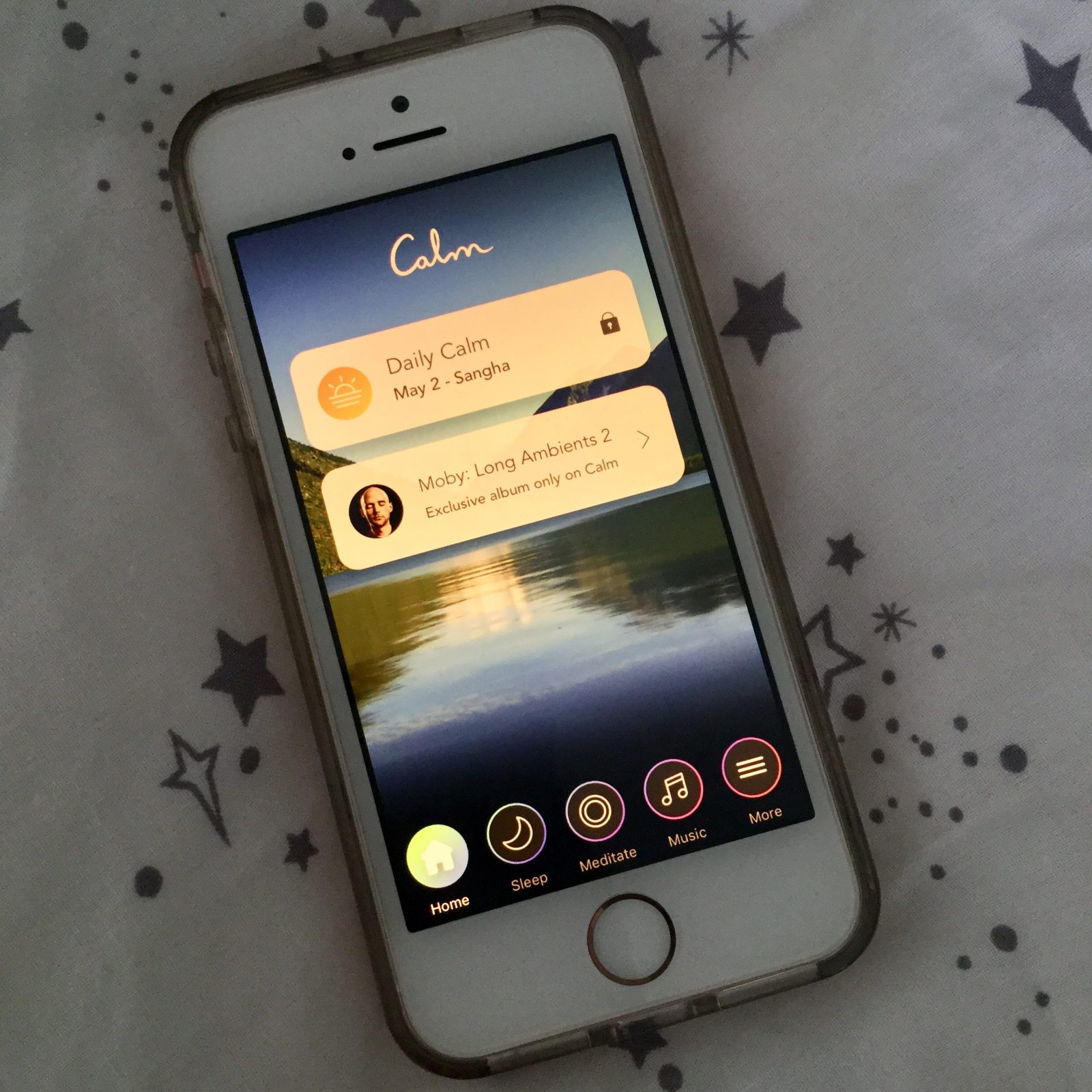 iphone on bedsheets displaying calm app home screen