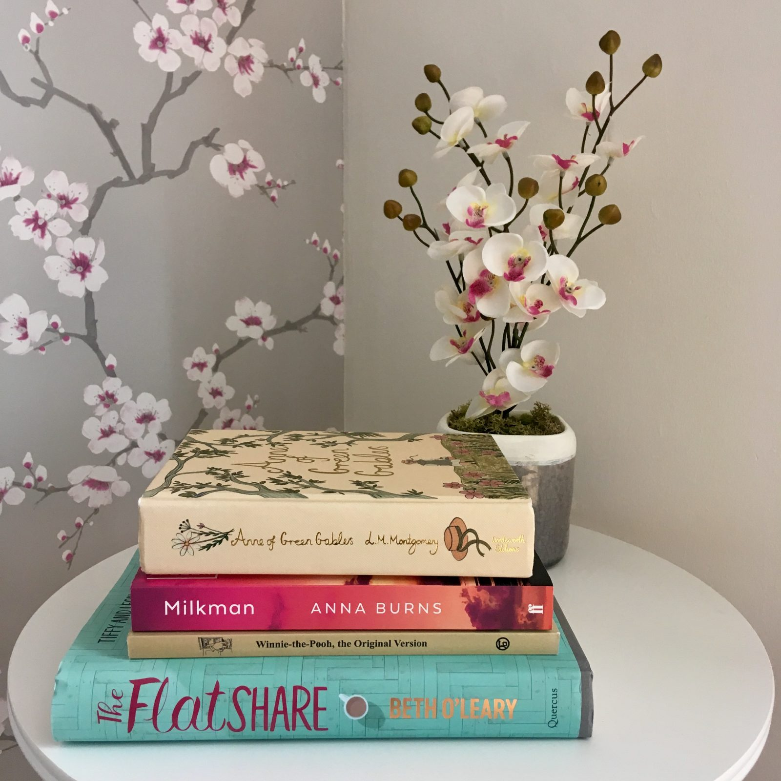 pile of books with spines visible, placed on white table with decorative flower in the background
