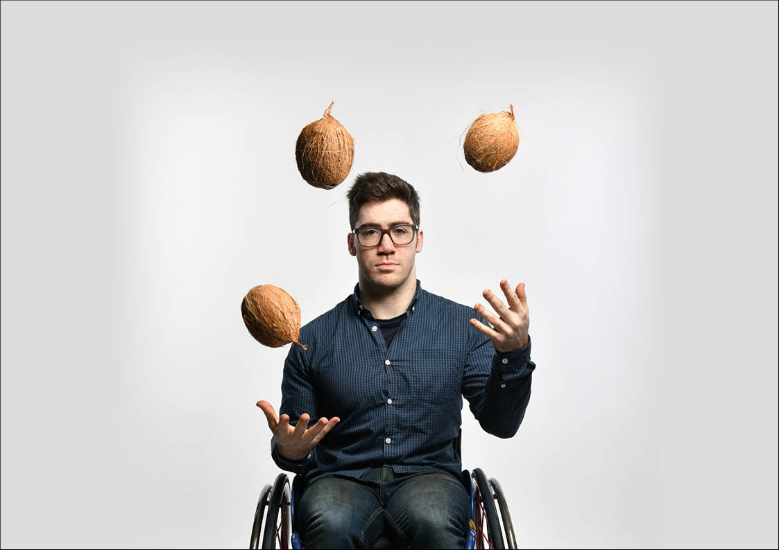press image of aaron simmonds in wheelchair, facing front and juggling coconuts