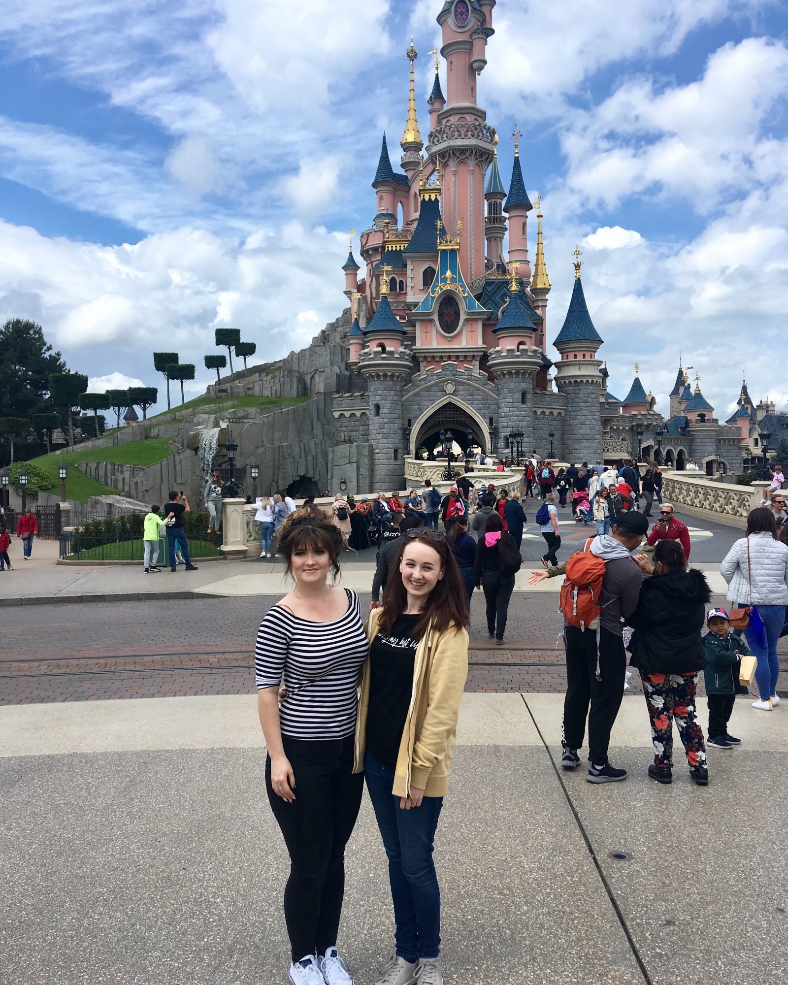 pippa and izzy stood outside in front of pink disneyland paris castle