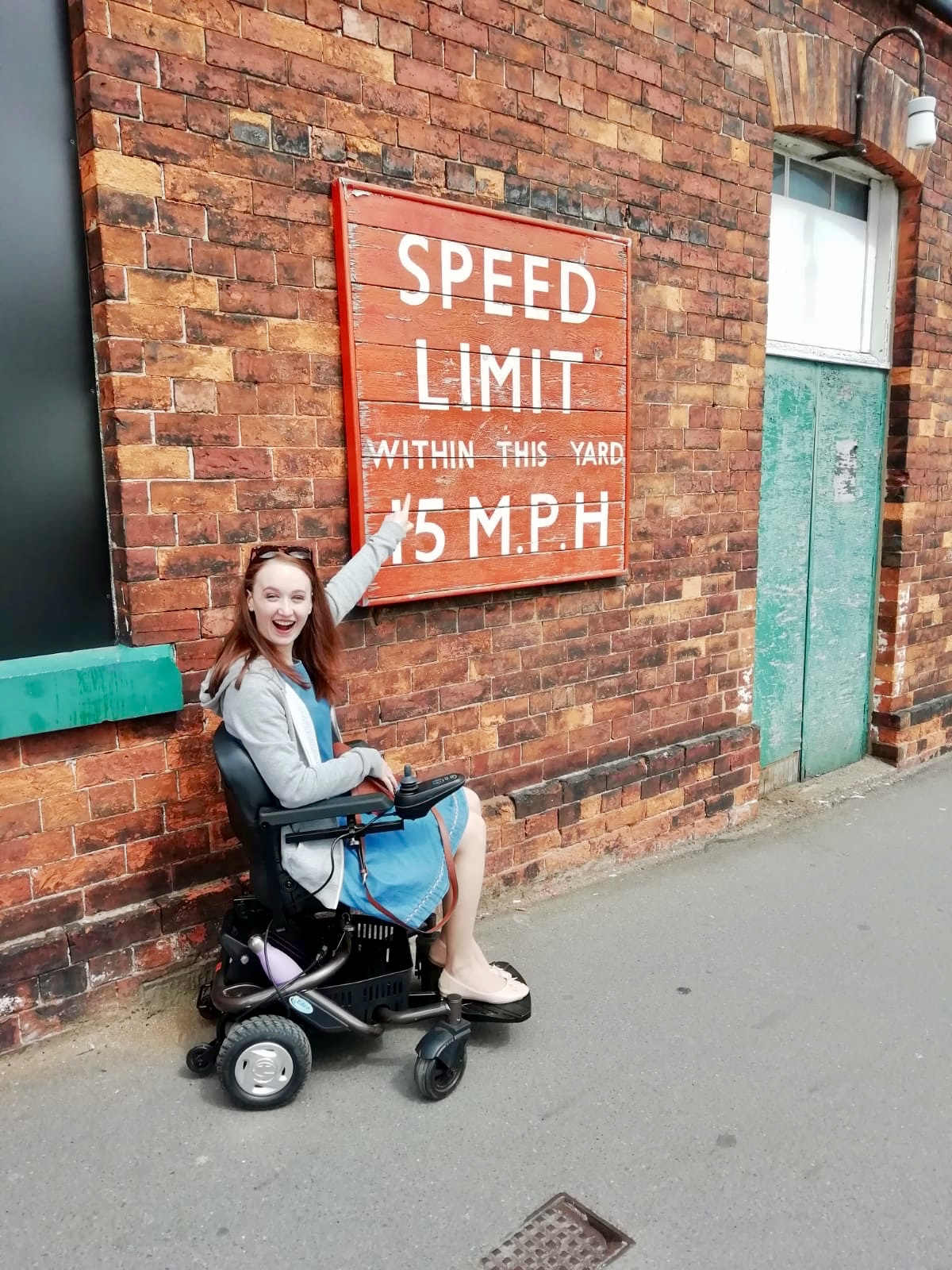 pippa in power-chair, pointing to outdoor sign reading 'speed limit within this yard 15MPH' and laughing