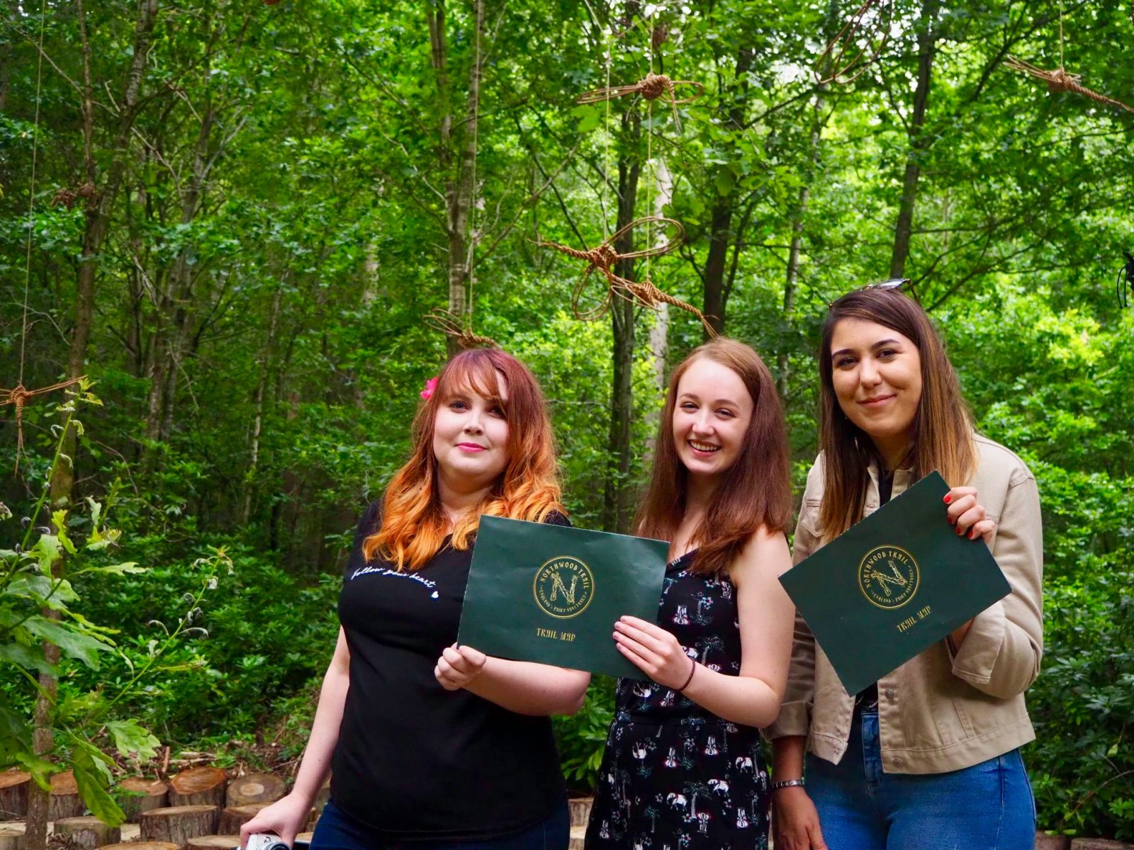 louise, pippa and natalie, standing up and holding trail maps, surrounded by green forest