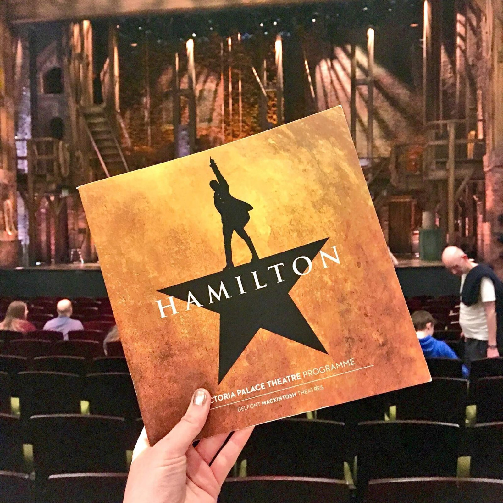 hand holding yellow square hamilton theatre programme, with hamilton stage and set visible in the background