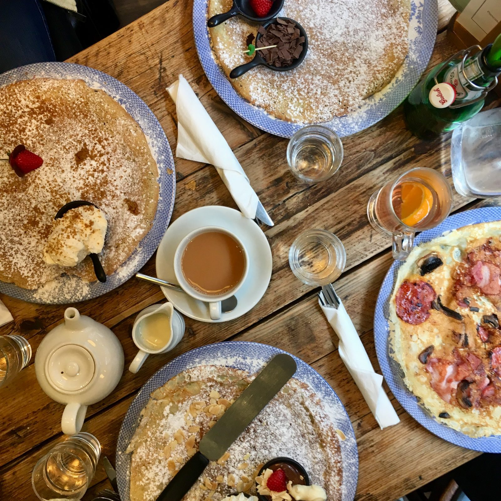 flatlay of four breakfast pancakes and hot drinks at double dutch pancake house