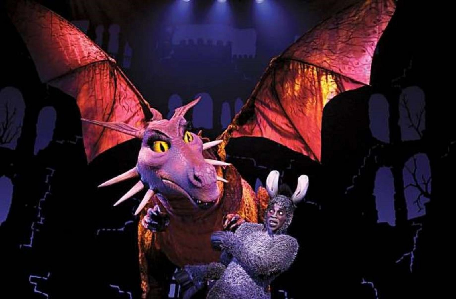 production image of donkey cowering away from large dragon puppet looking down at him