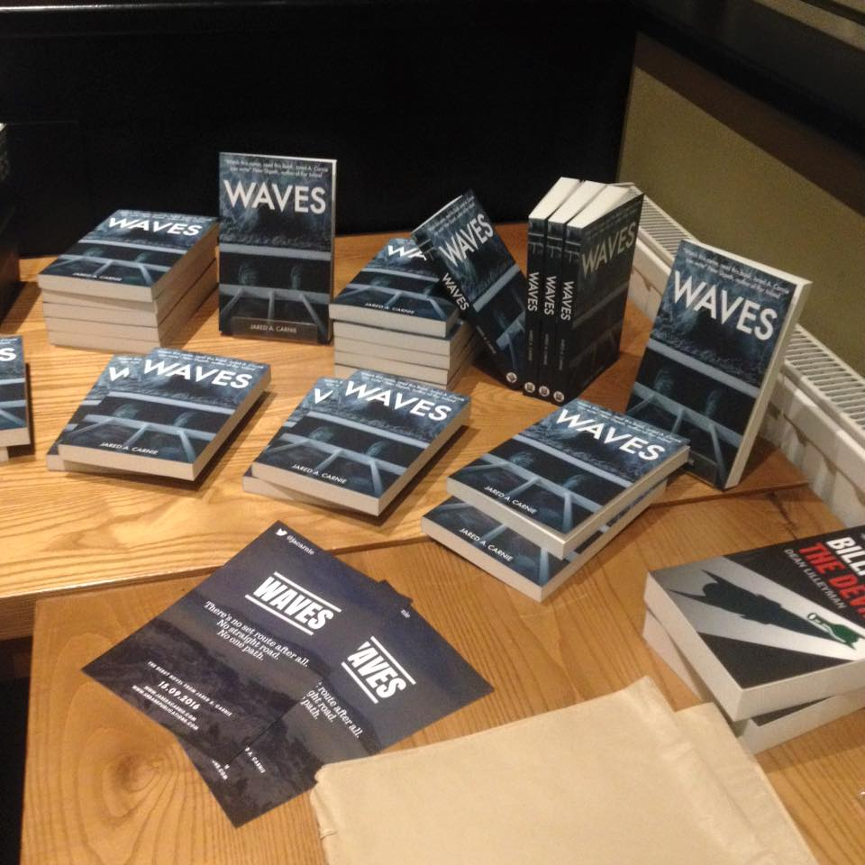 copies of waves book piled on table at book launch