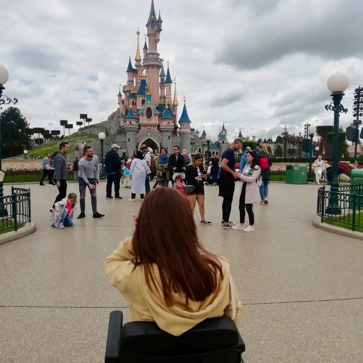 pippa in powerchair with back to camera, disneyland paris castle in background