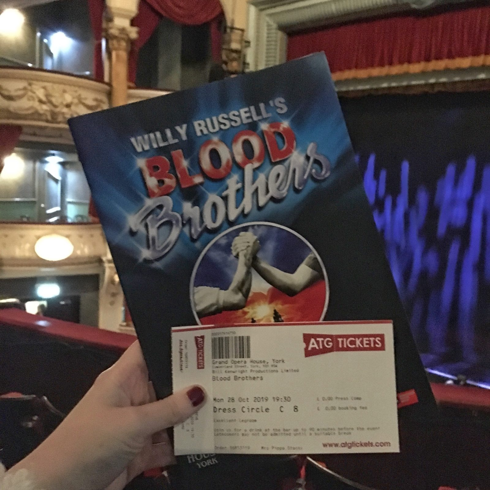 pippa's hand holding up blood brothers programme and ticket, with theatre in background