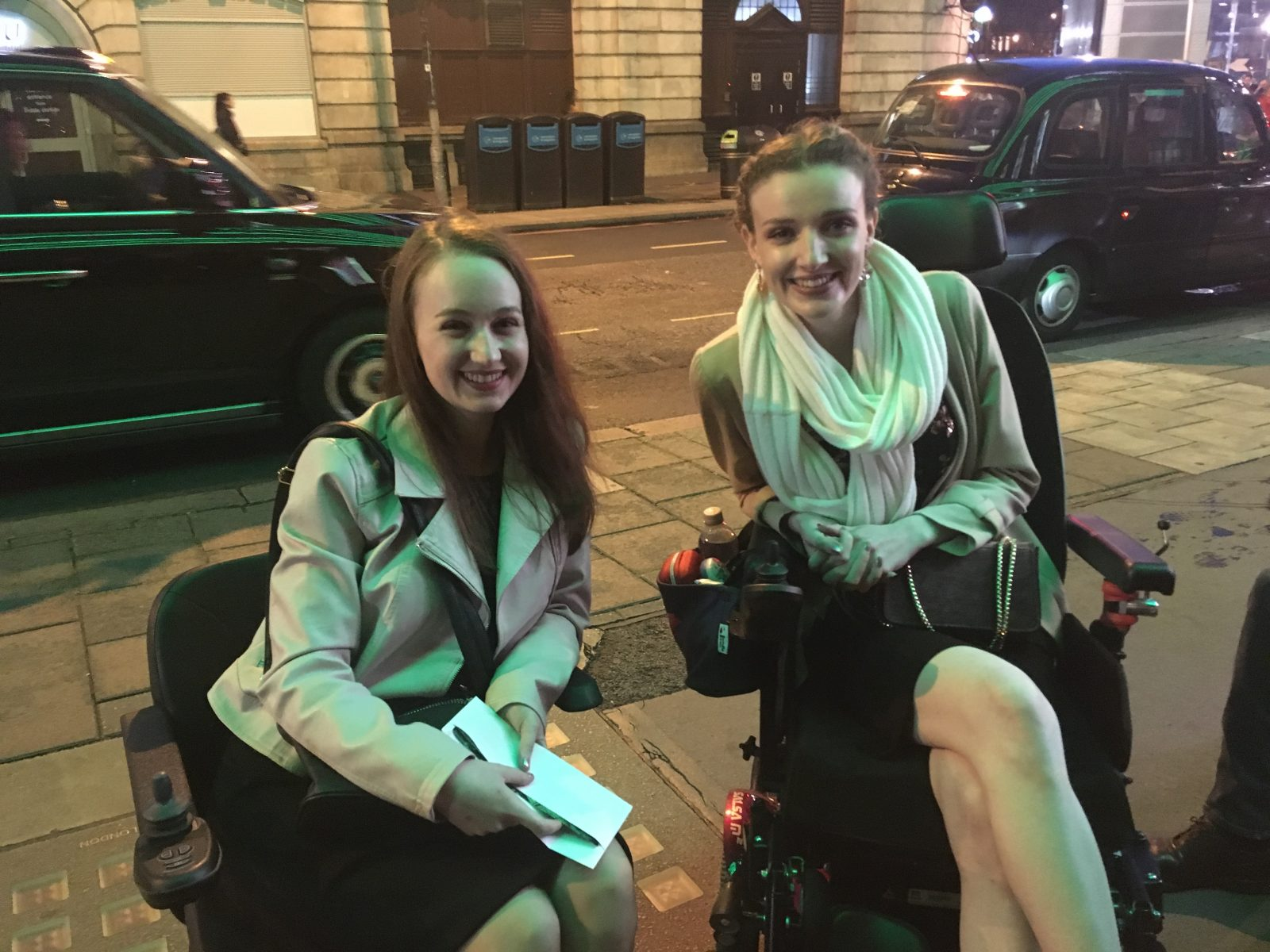 pippa and kate both sat in powerchairs and smiling, outdoors