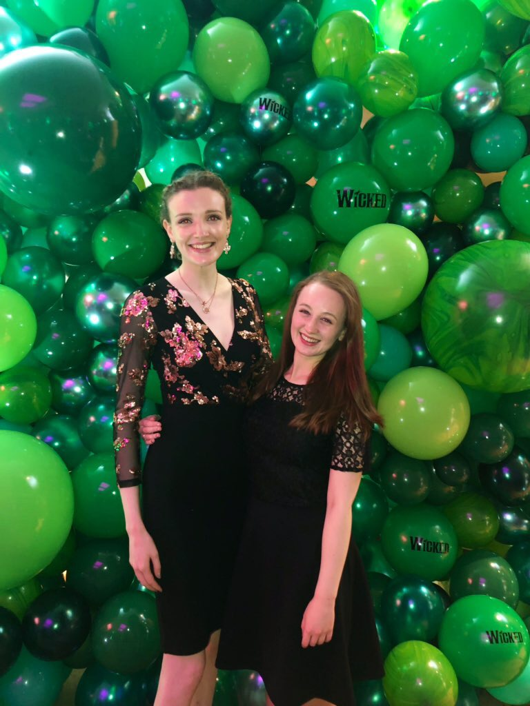 Pippa and Kate stood up in front of green balloon photo wall