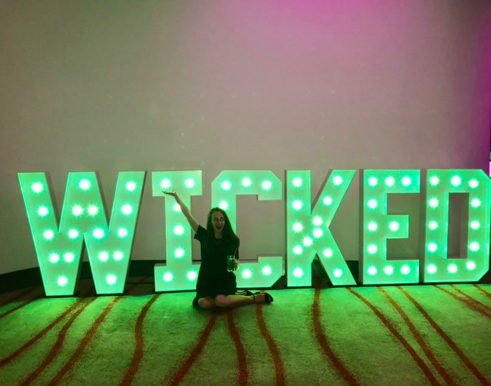 pippa sat on floor posing in front of LED wicked green sign