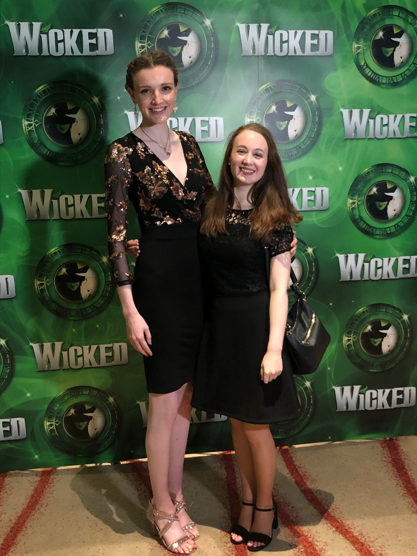 kate and pippa stood in front of official wicked photo backdrop