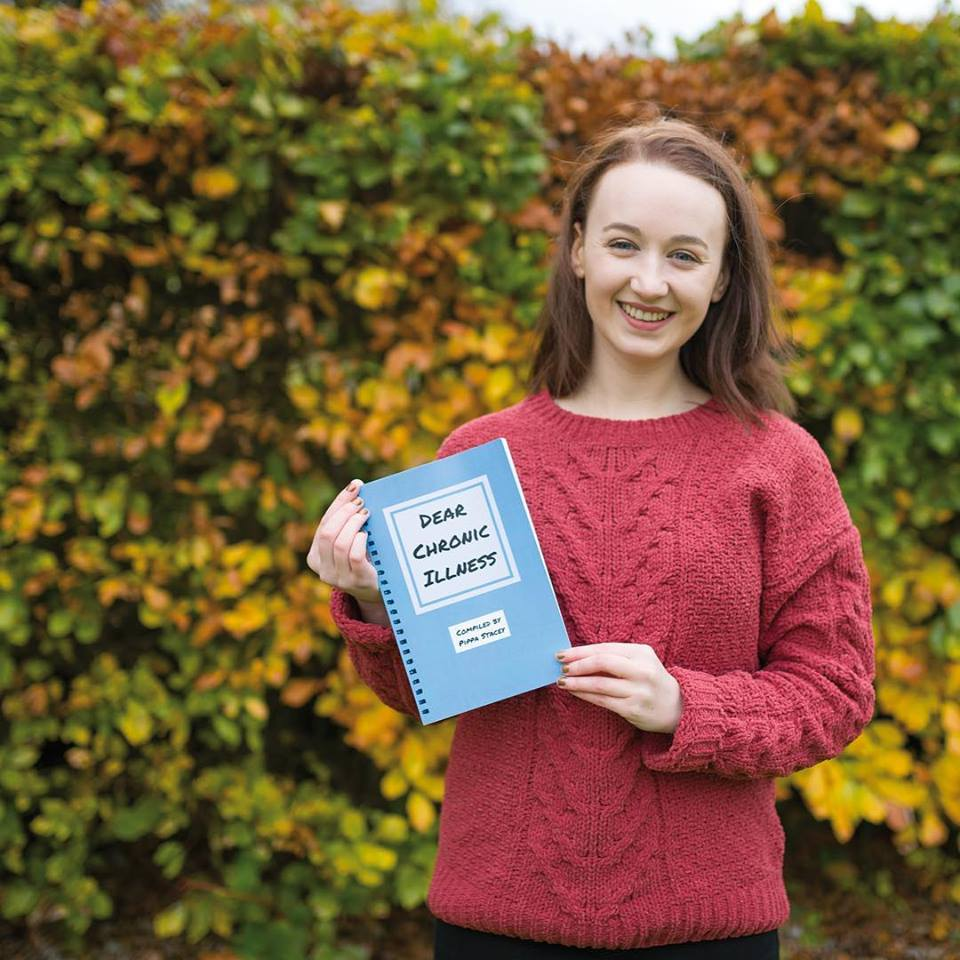 pippa wearing read jumper and holding blue 'dear chronic illness' book