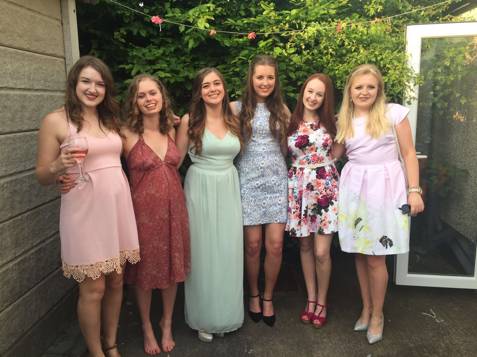 pippa and five university friends, stood outdoors in formal dresses and smiling