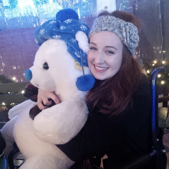 pippa in wheelchair, holding giant white teddybear and smiling