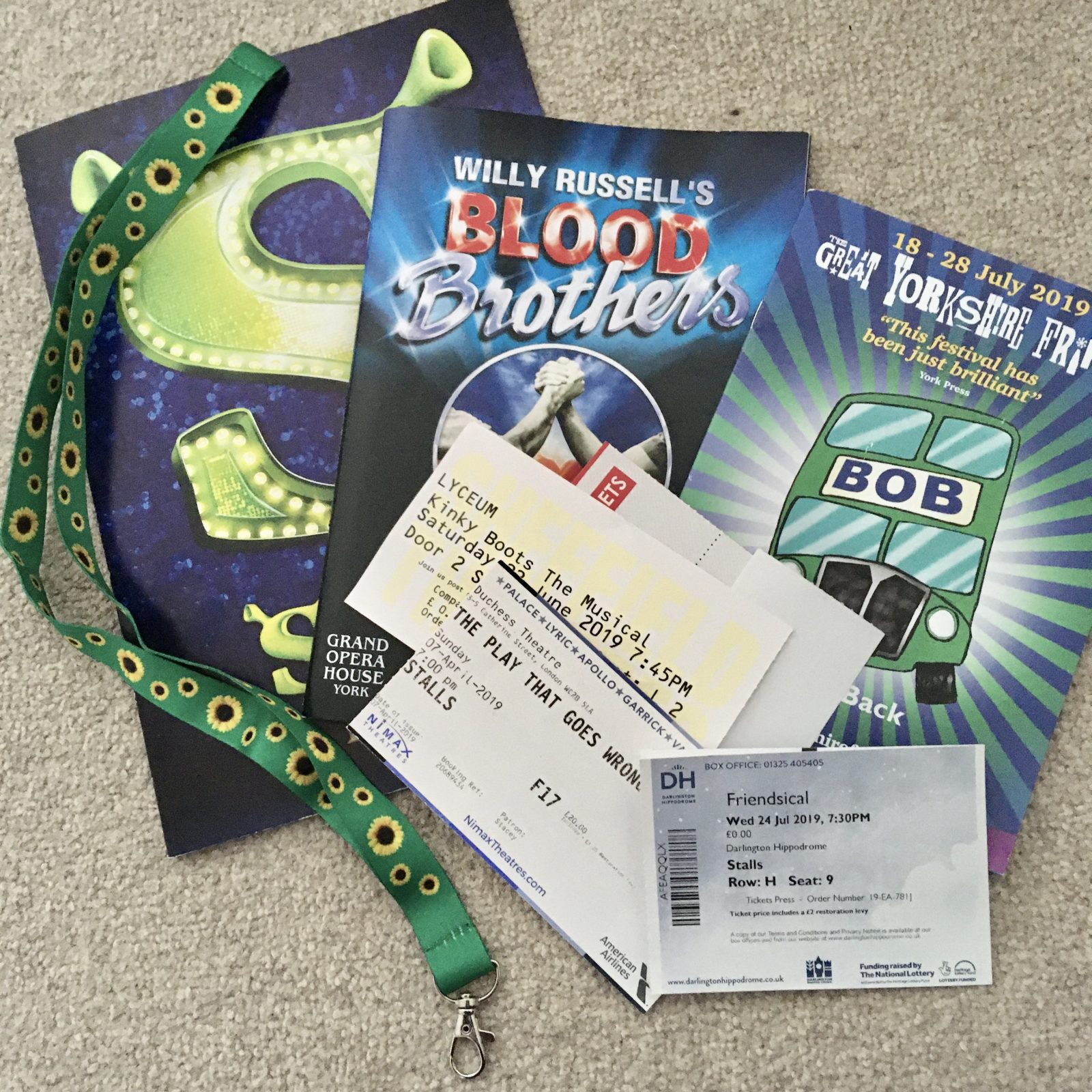 theatre programmes and tickets laid on floor, with green sunflower lanyard draped over the top