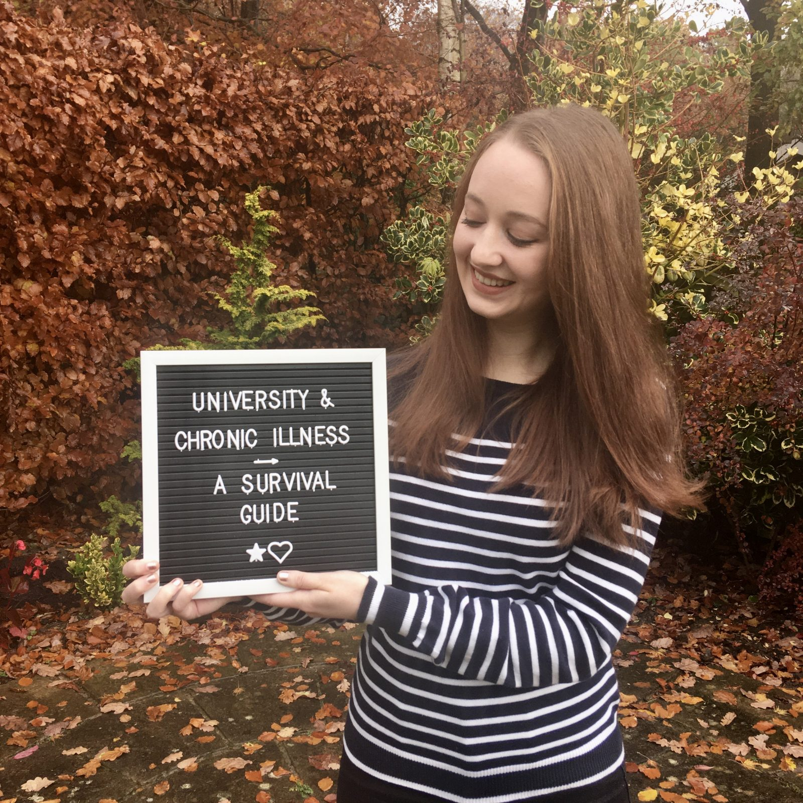headshot of pippa outdoors, looking down and holding letterboard sign reading 'university and chronic illness: a survival guide'
