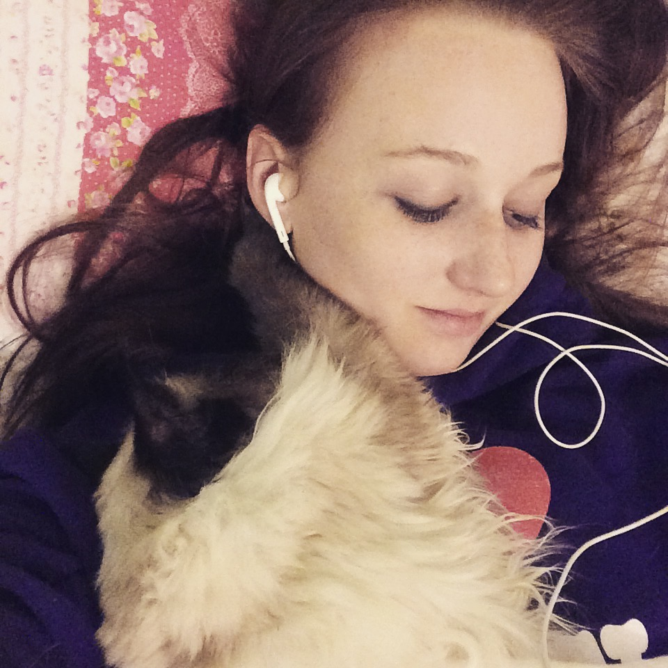 pippa paid in bed looking down, headphones in ears and cat laid on top of her