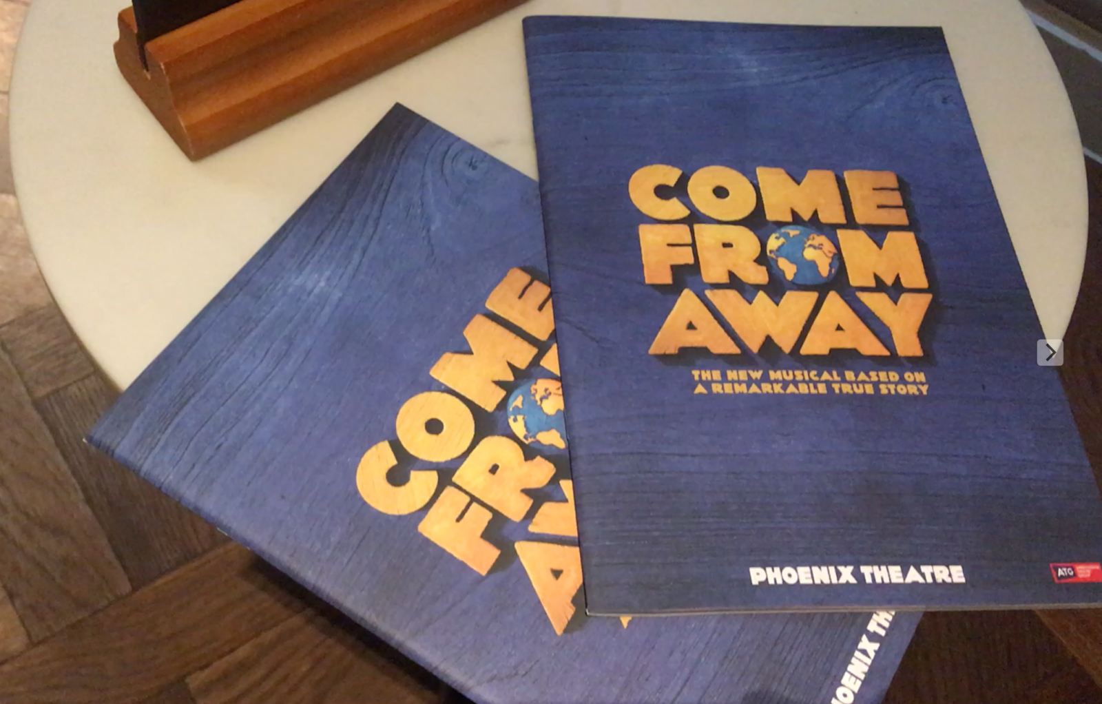 come from away programmes resting on table in bar