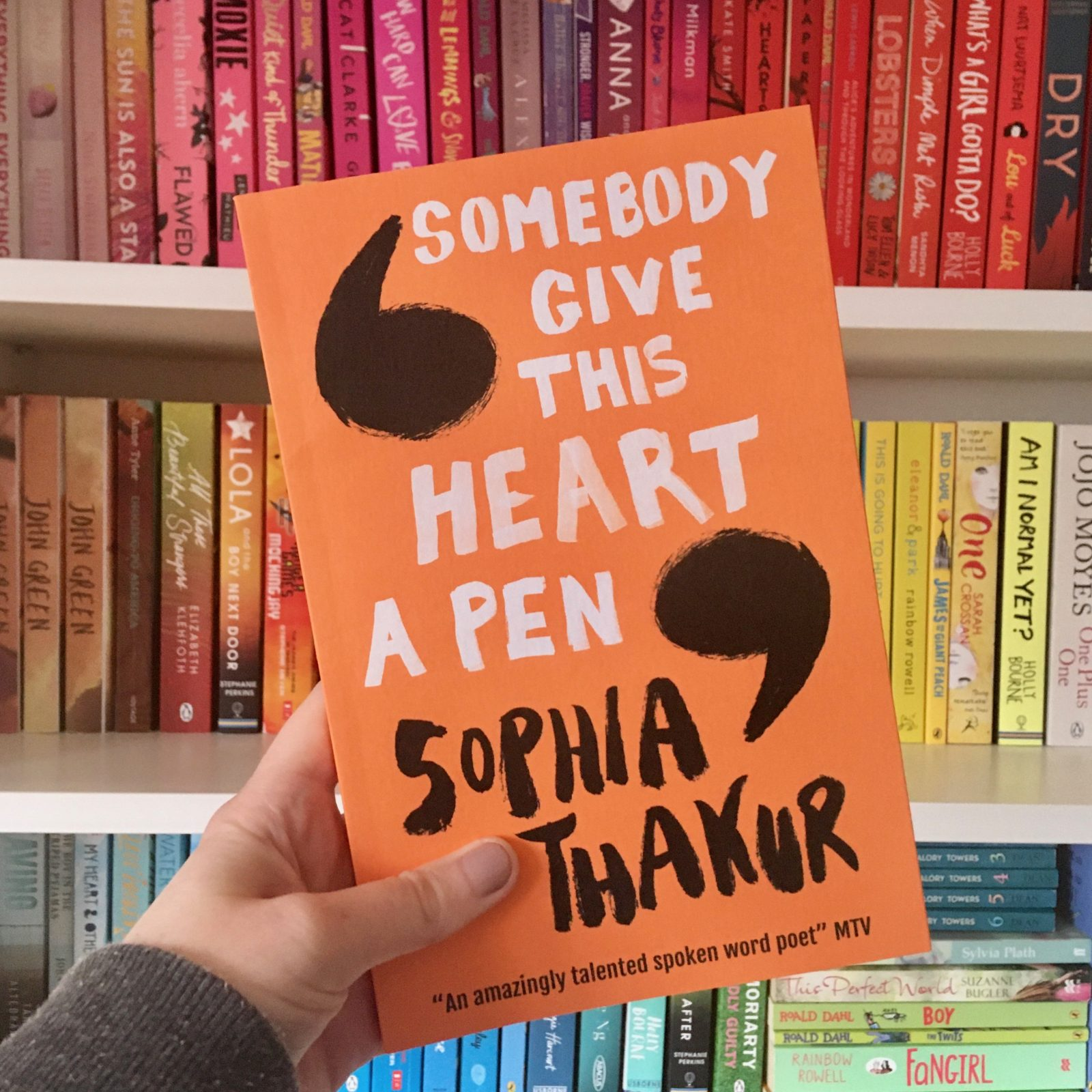 hand holding orange 'somebody give this heart a pen' book in front of rainbow bookshelves