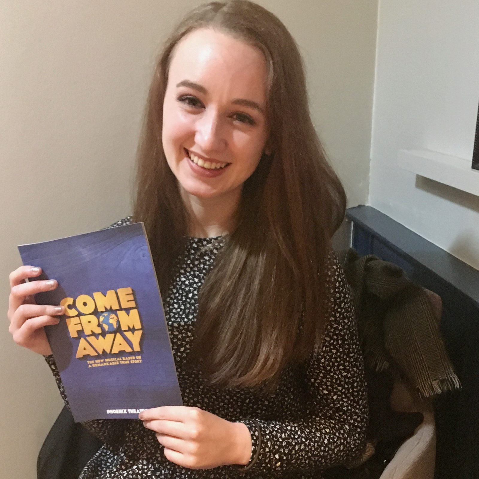 pippa sat on chair, holding up blue come from away programme and smiling