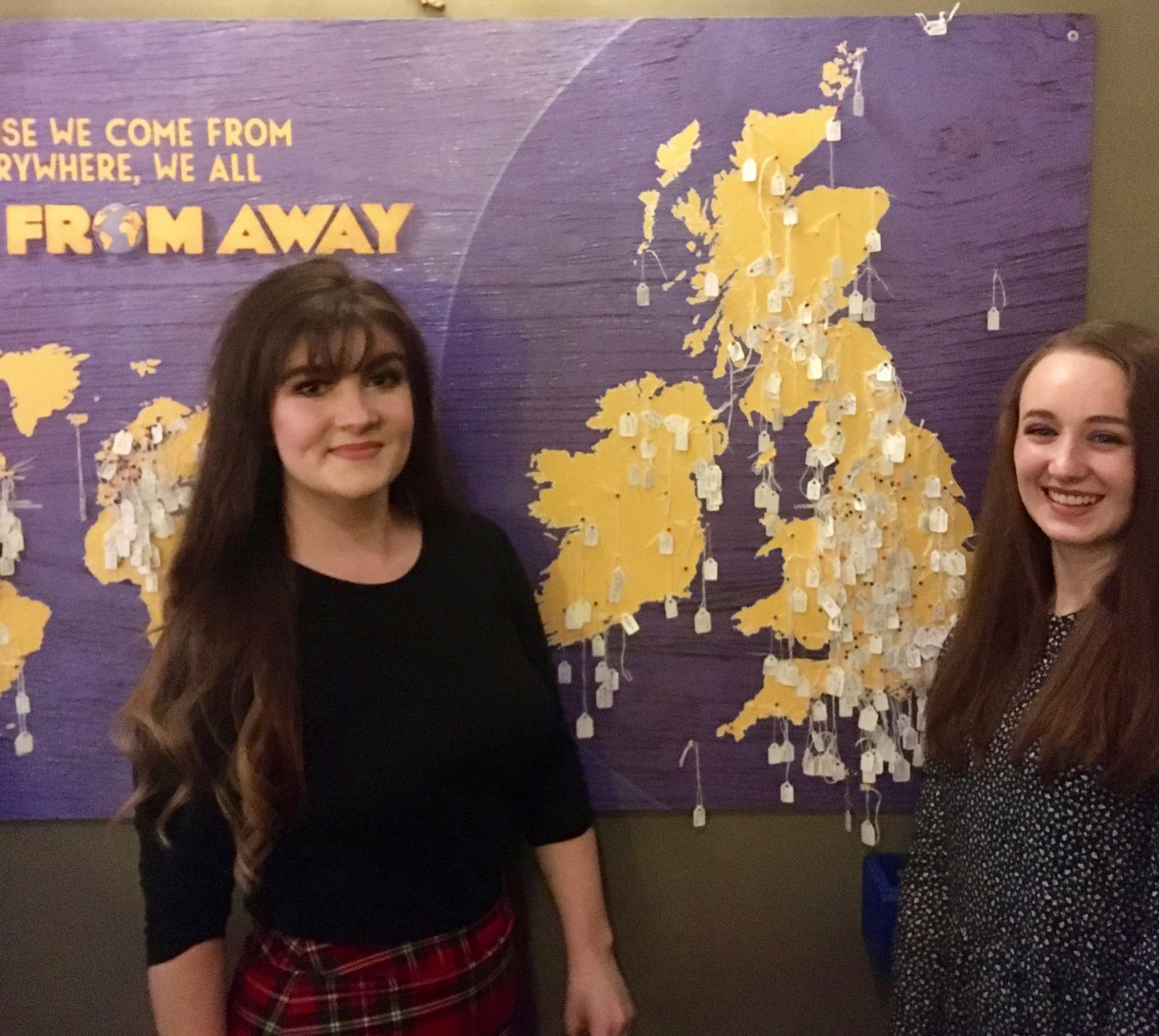 pippa and izzy stood in front of come from away pinboard visitor map