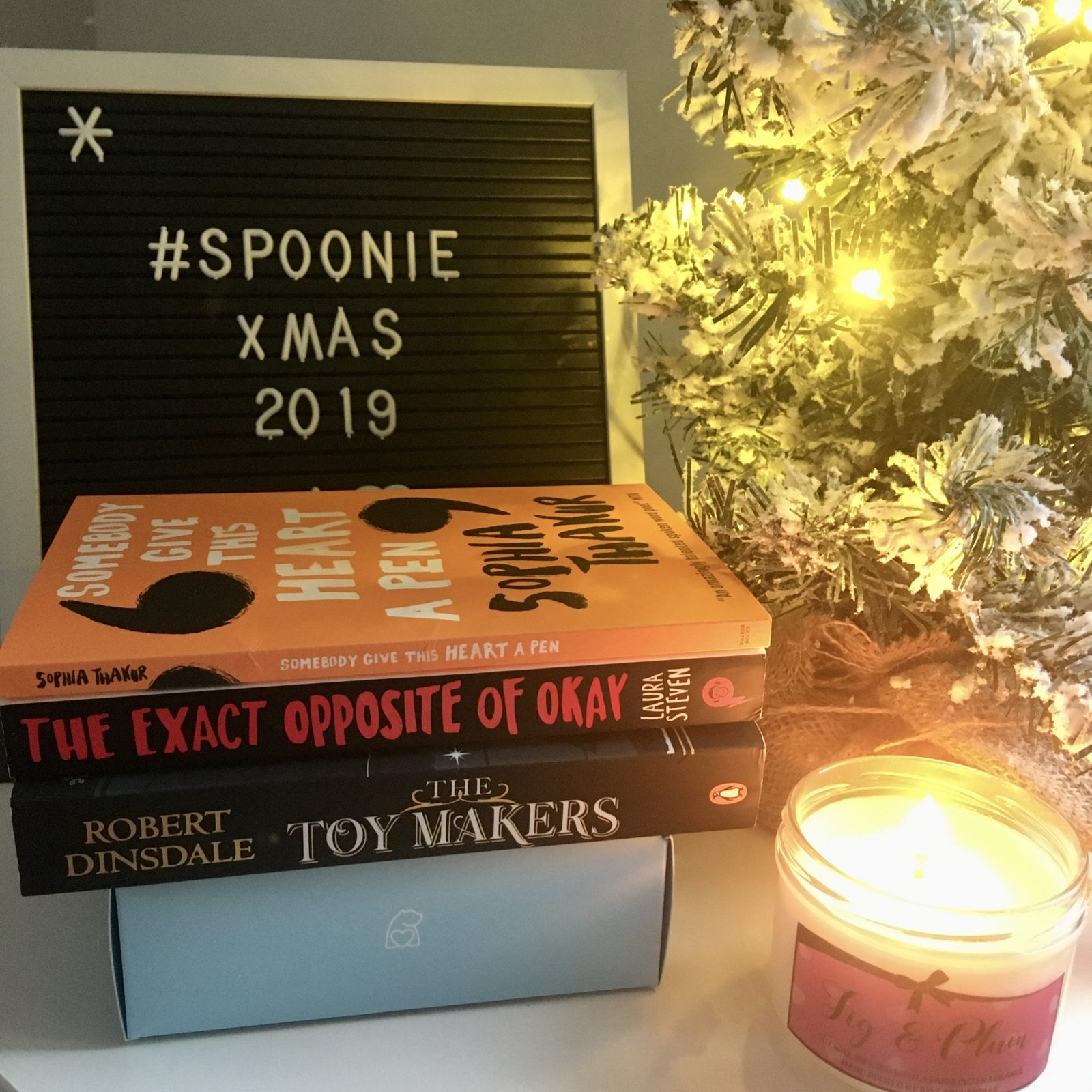 pile of three books in front of 'spoonie xmas' letterboard, next to lit candle and mini christmas tree