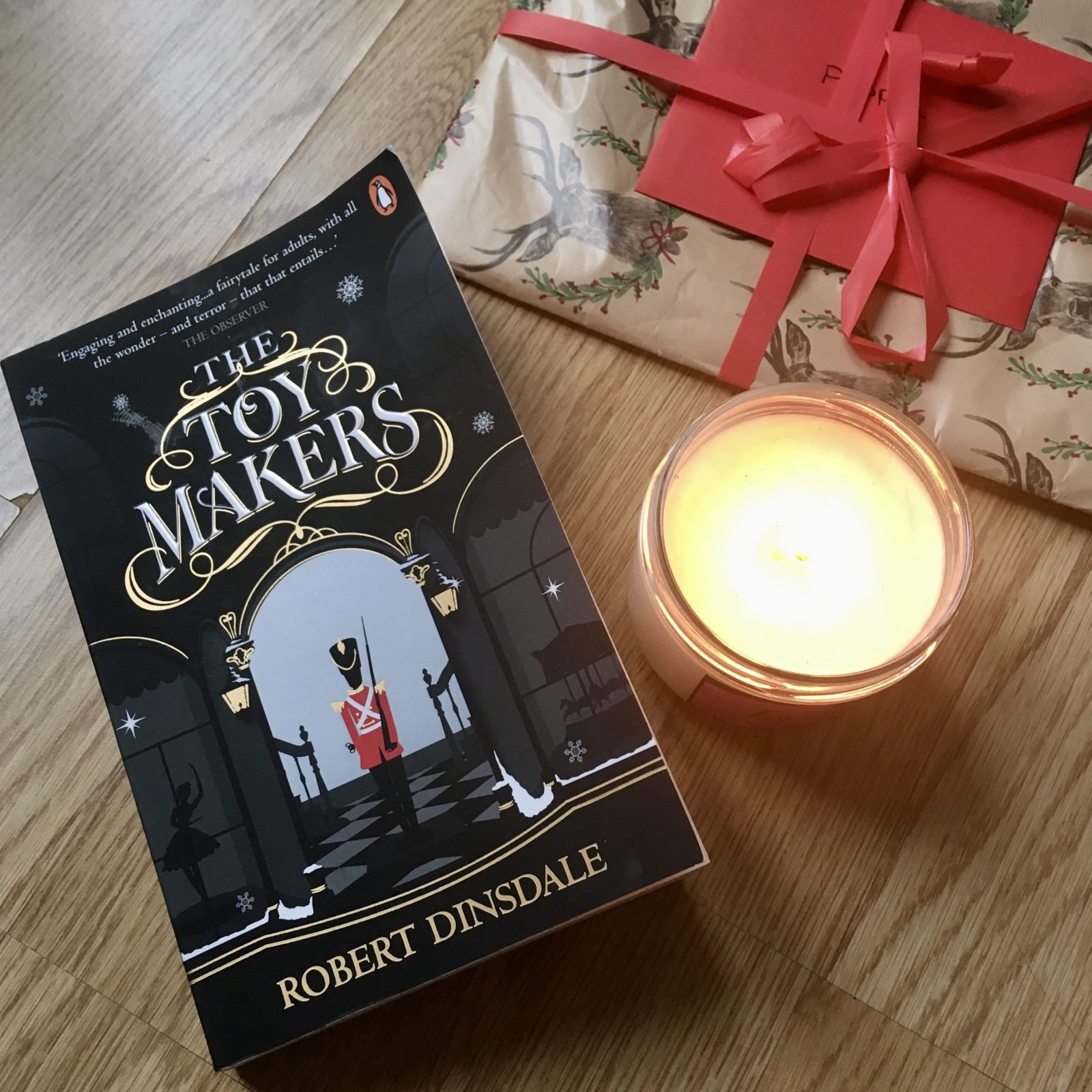 copy of 'the toymakers' on wooden floor, next to lit candle and wrapped christmas present