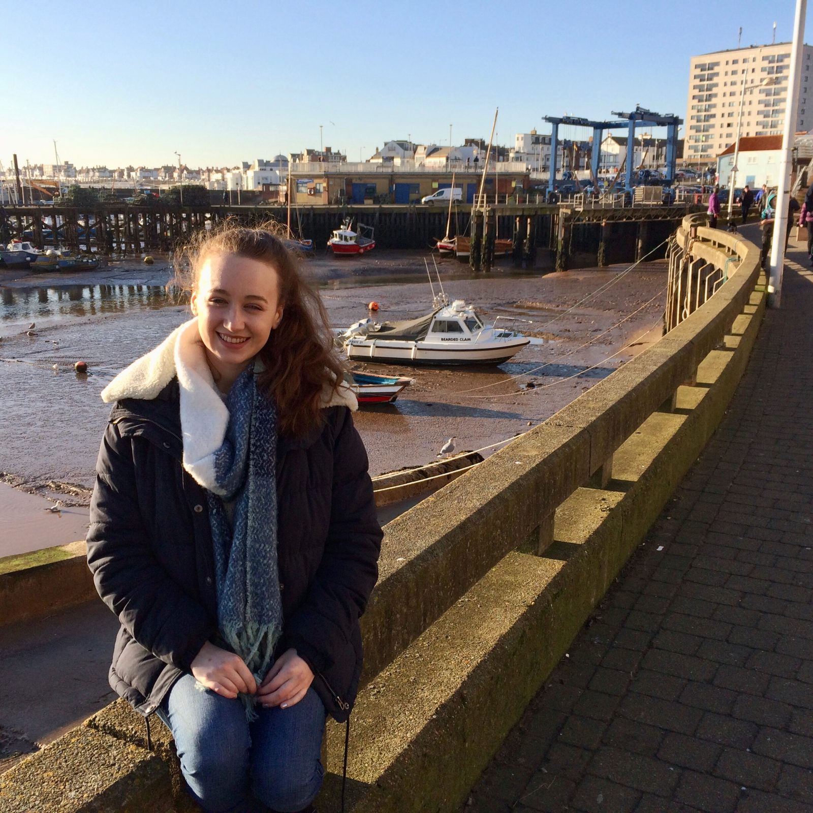pippa sat outdoors wearing coat and scarf, harbour visible in background