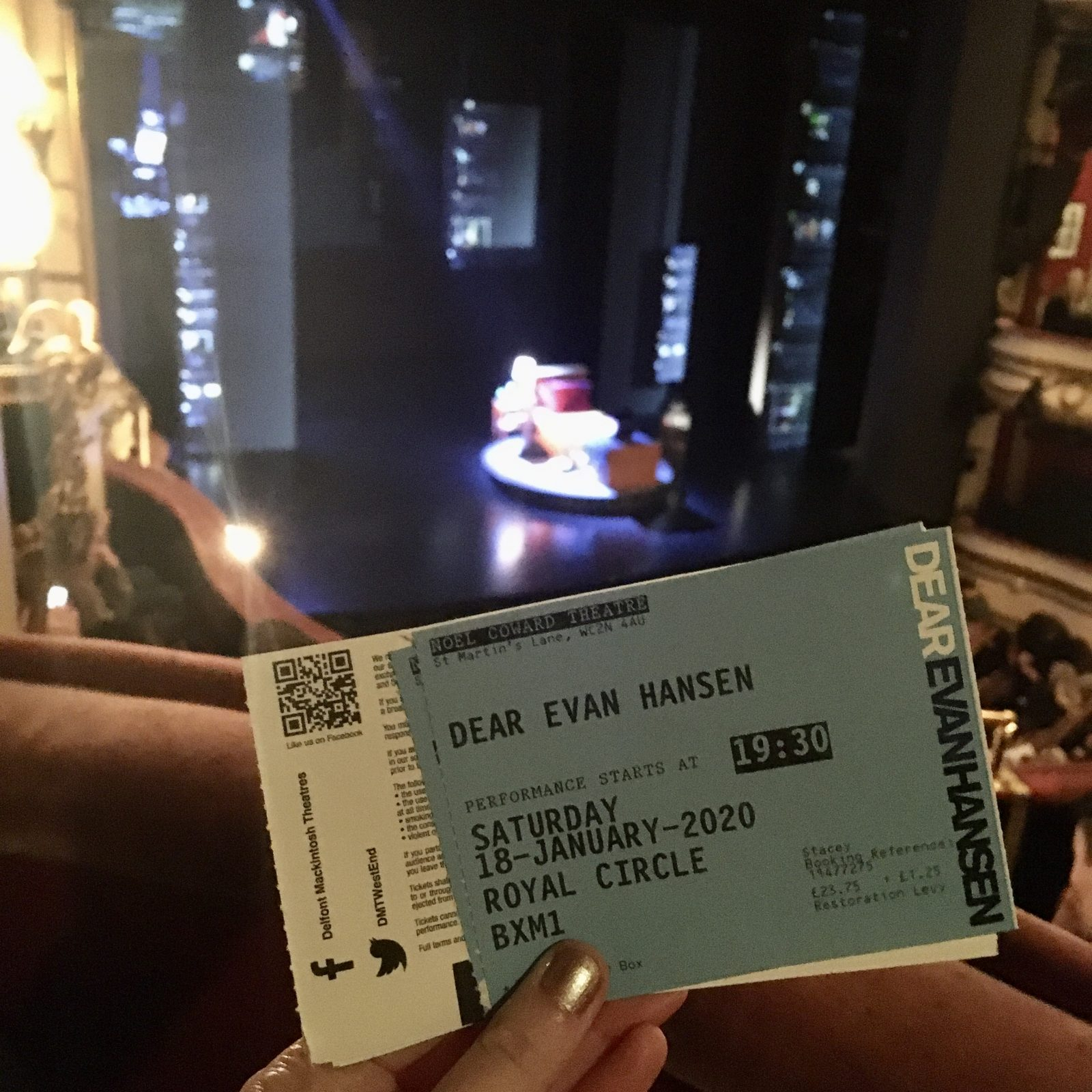 pippa's hand holding up blue dear evan hansen ticket, with stage and audience visible in background