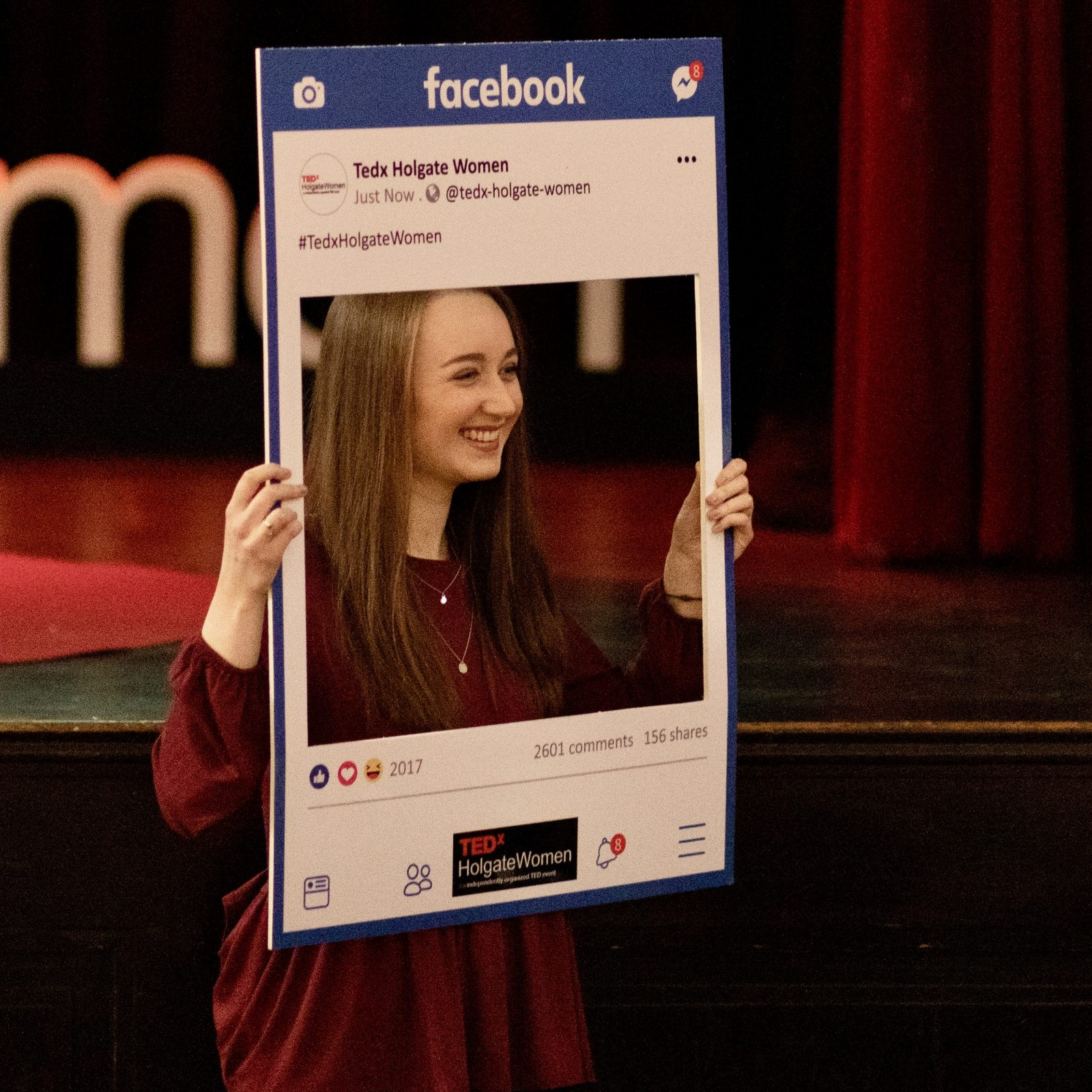 pippa stood holding up social media-style facebook photo board and smiling as somebody else takes a picture of her