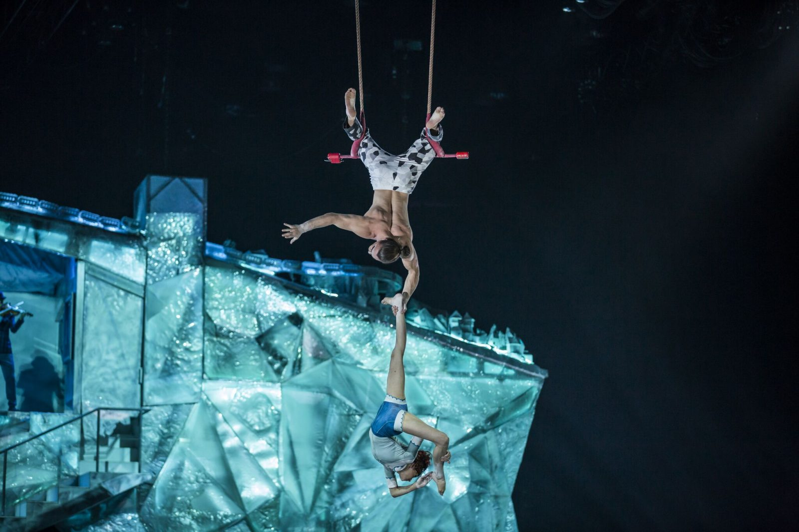 performer hanging from trapeze by his feet, holding onto one leg of female performer hanging beneath him and bringing other leg up to head