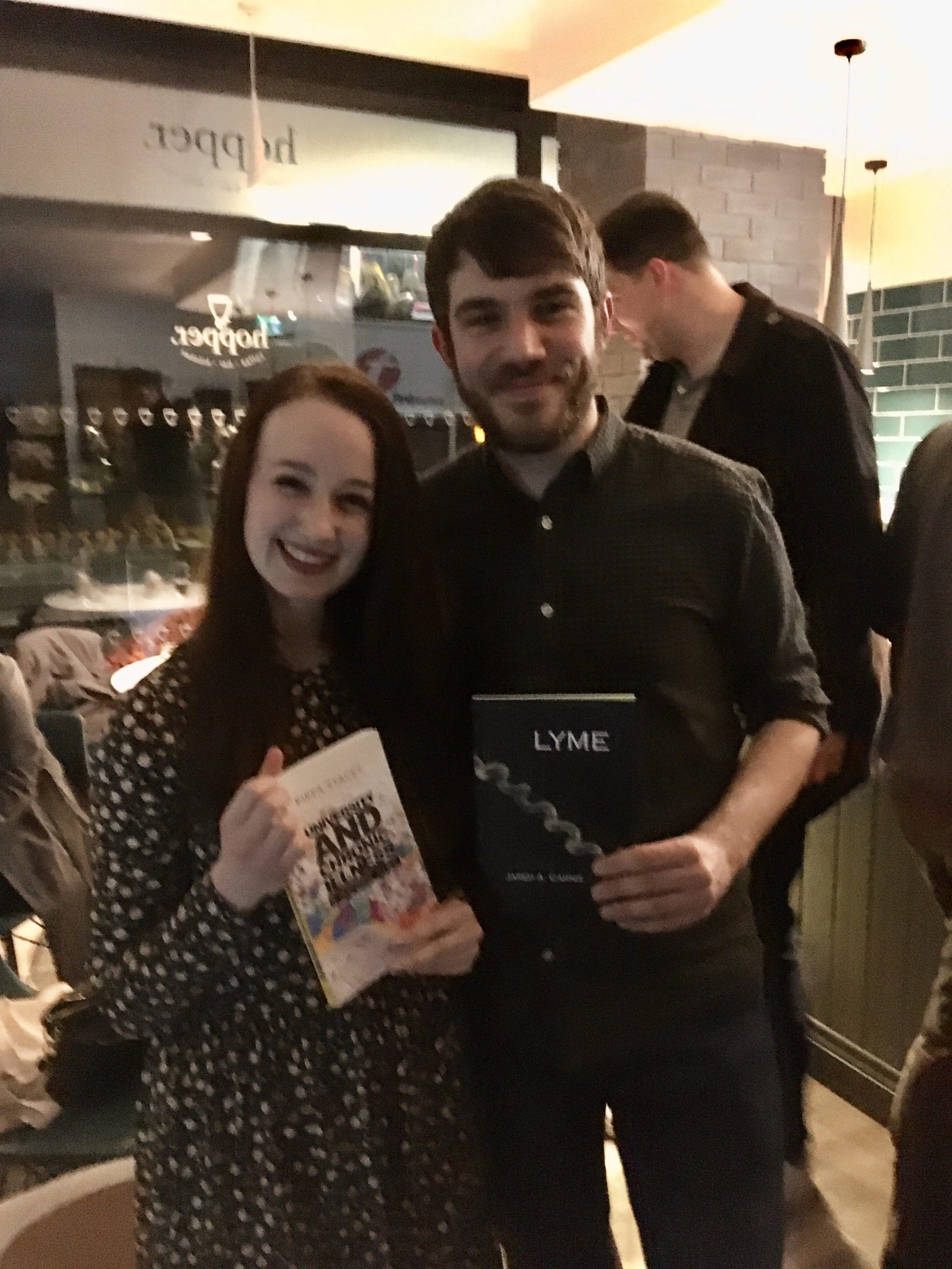 pippa and jared stood up next to each other at book launch event, each holding copies of their own book and smiling