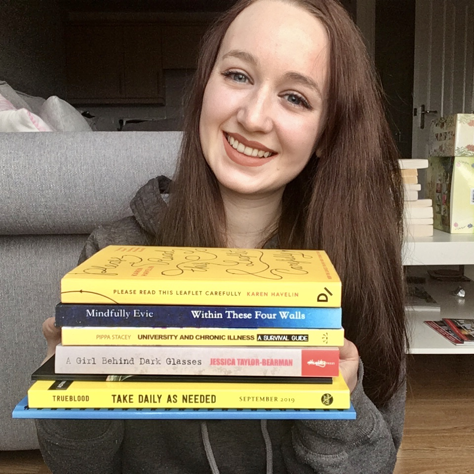 pippa holding up stack of colourful chronic-illness inspired books and smiling