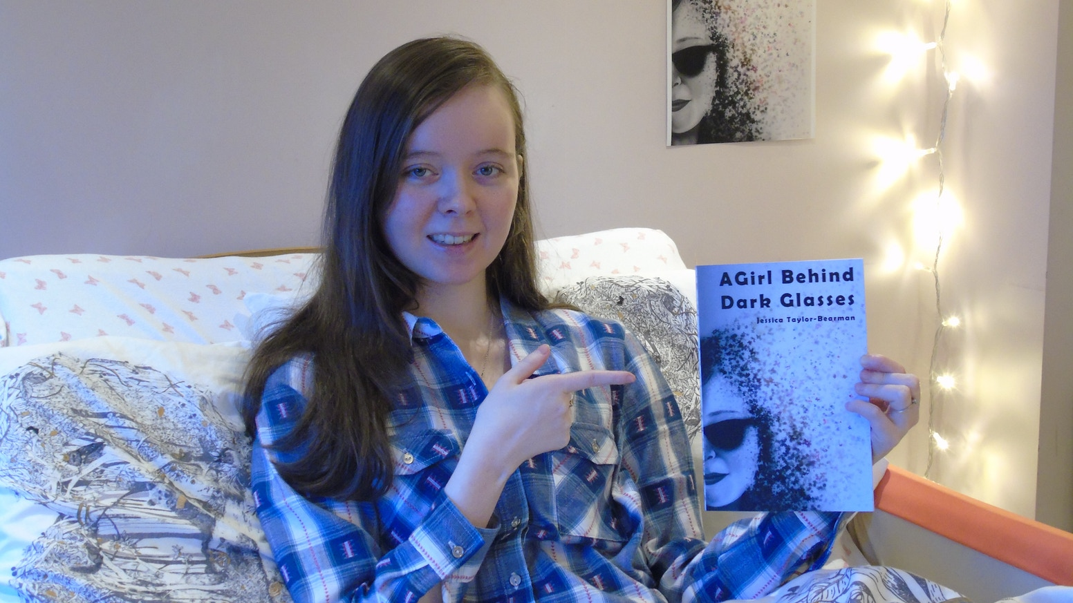 jessica taylor bearman in bed, wearing pyjamas and pointing to other hand, holding grey 'a girl behind dark glasses' book