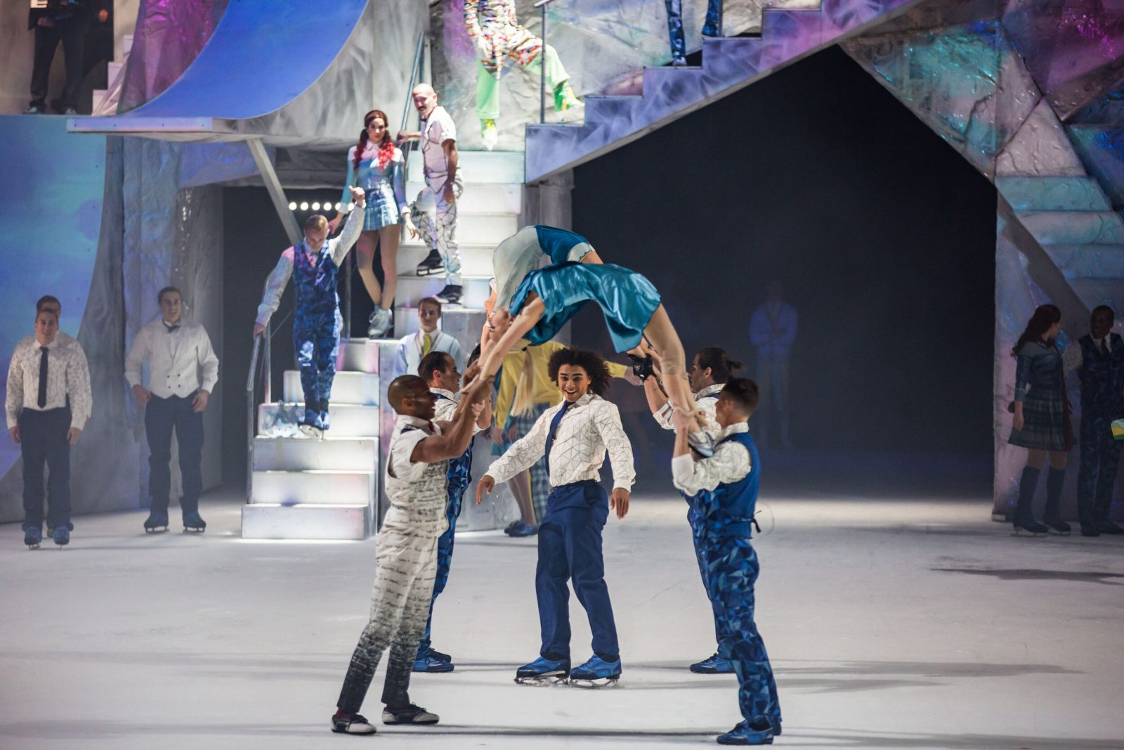 cast members holding up females in backbend position, with skaters dancing underneath the arches their backs make