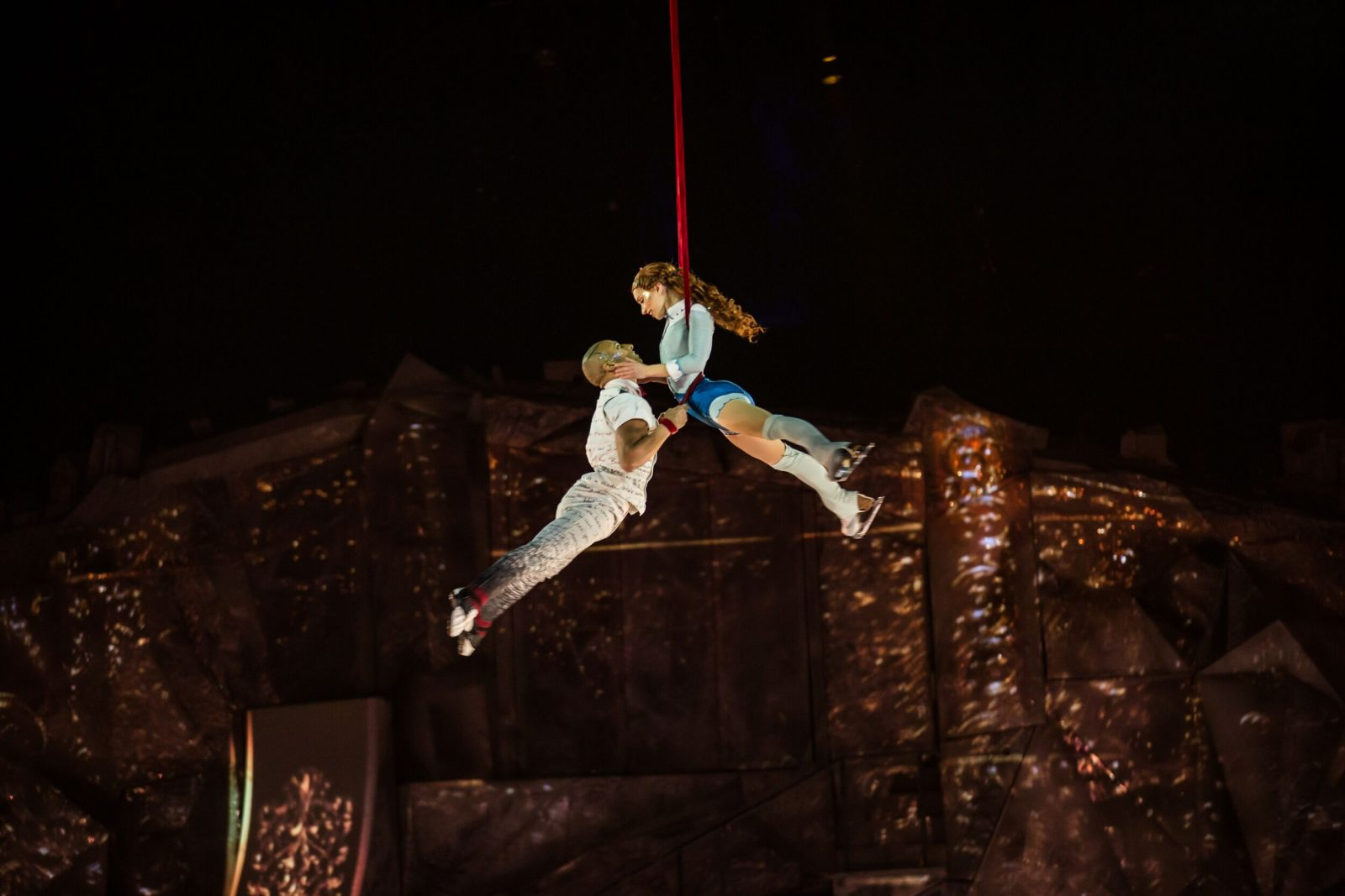 male and female performer hanging onto each other with legs raised, suspended in the air by red silk