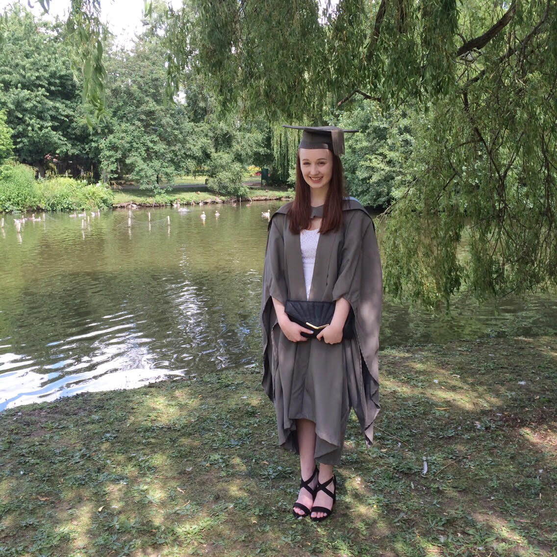 pippa wearing white dress with graduation cap and gown in grey, stood up outdoors with trees and river in background, holding black clutch bag and smiling