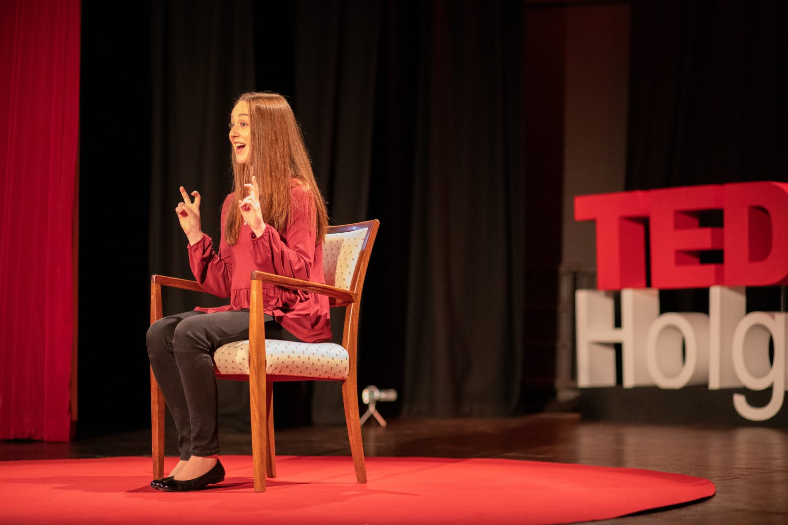 pippa on stage at tedx, sat on chair and making strange hand gesture whilst talking to audience