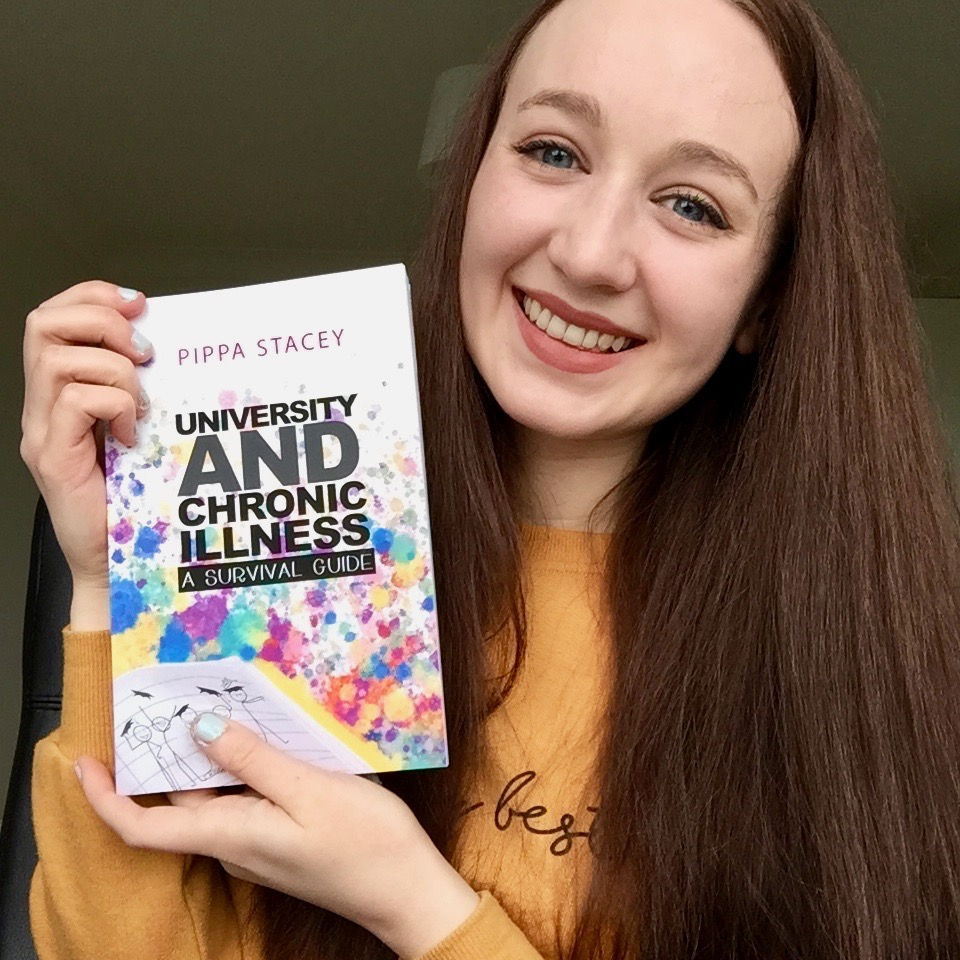 "headshot of pippa in yellow jumper, holding up paperback copy of ""university and chronic illness: a survival guide"" book and smiling"