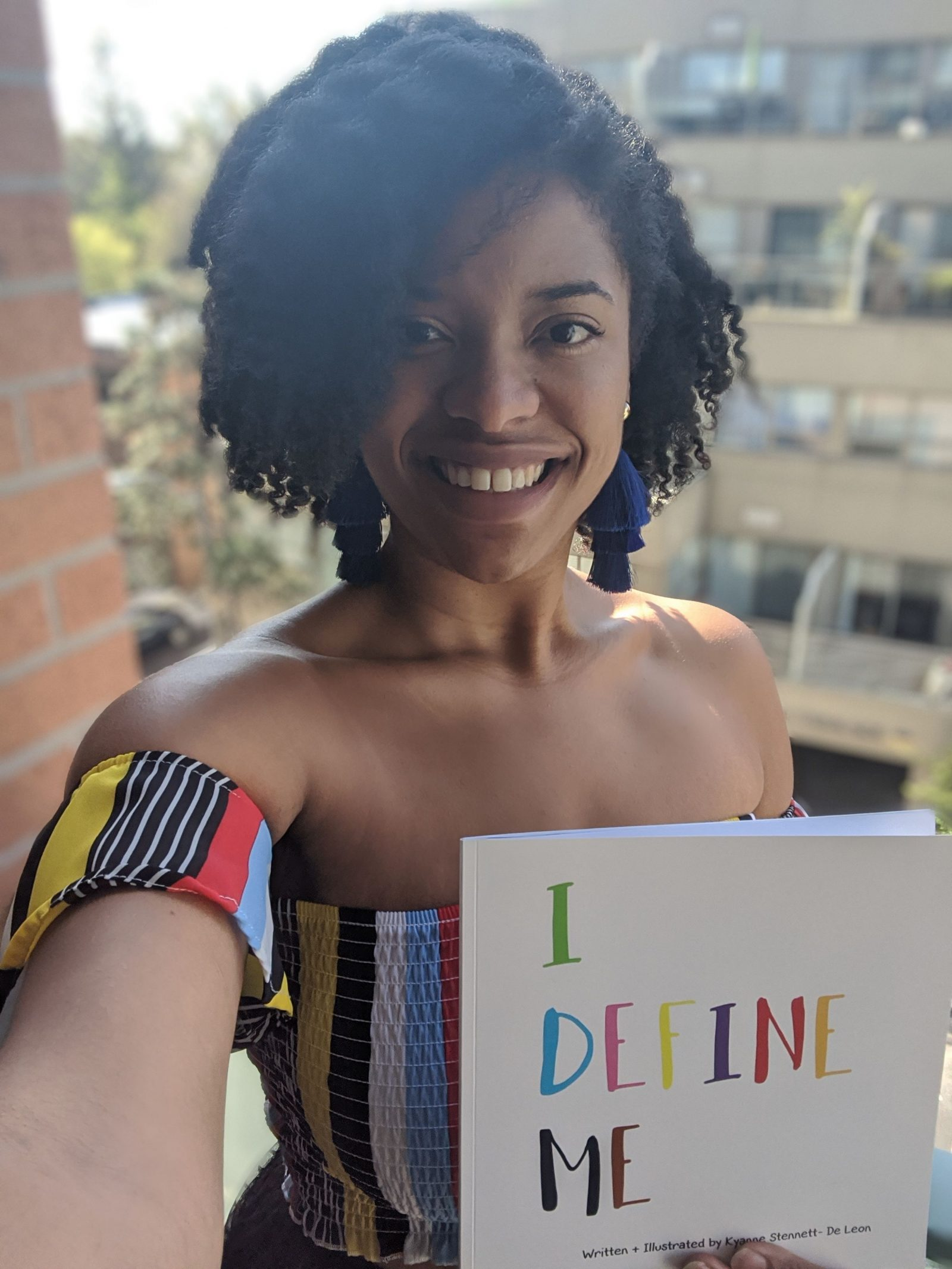 selfie of Kyanne on balcony, wearing stripy top and holding up copy of 'I define me' children's book
