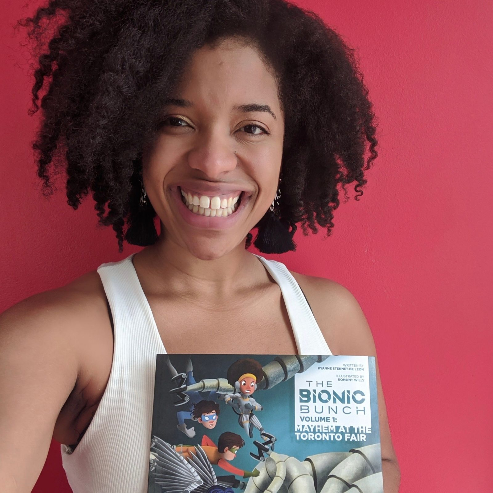 headshot selfie of kyanne stennett holding up 'the bionic bunch' children's book and smiling, against a red background