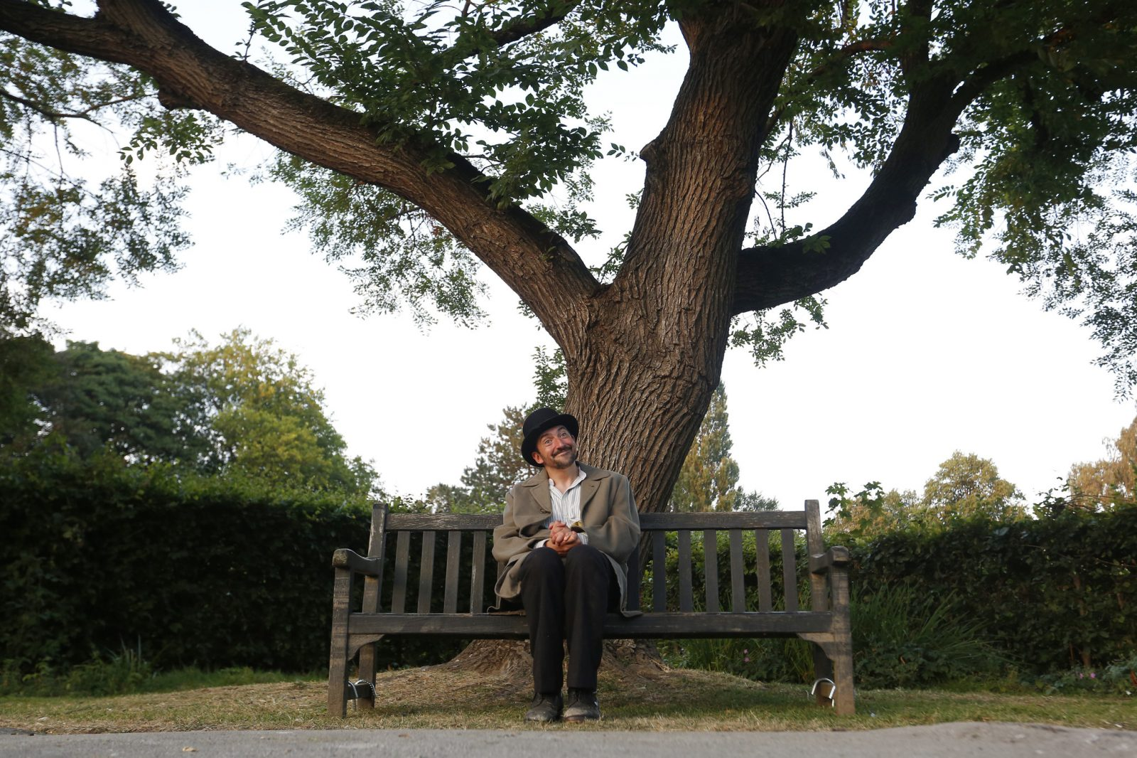 actor chris hannon in long tan coat and black hat, sat on park bench with legs together and head tilted to side
