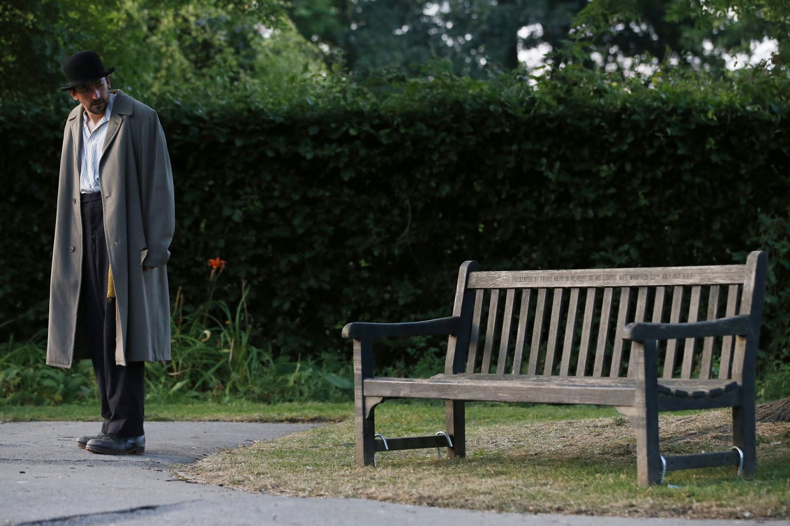 actor chris hannon in tan overcoat and black hat, standing up and looking backwards towards empty park bench distanced slightly behind him