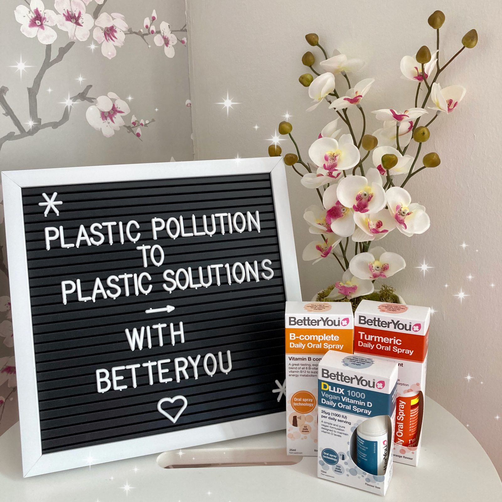 """black and white letterboard reading """"plastic pollution to plastic solutions with BetterYou"""" on white table next to decorative flowers and three of BetterYou's colourful transdermal sprays"""