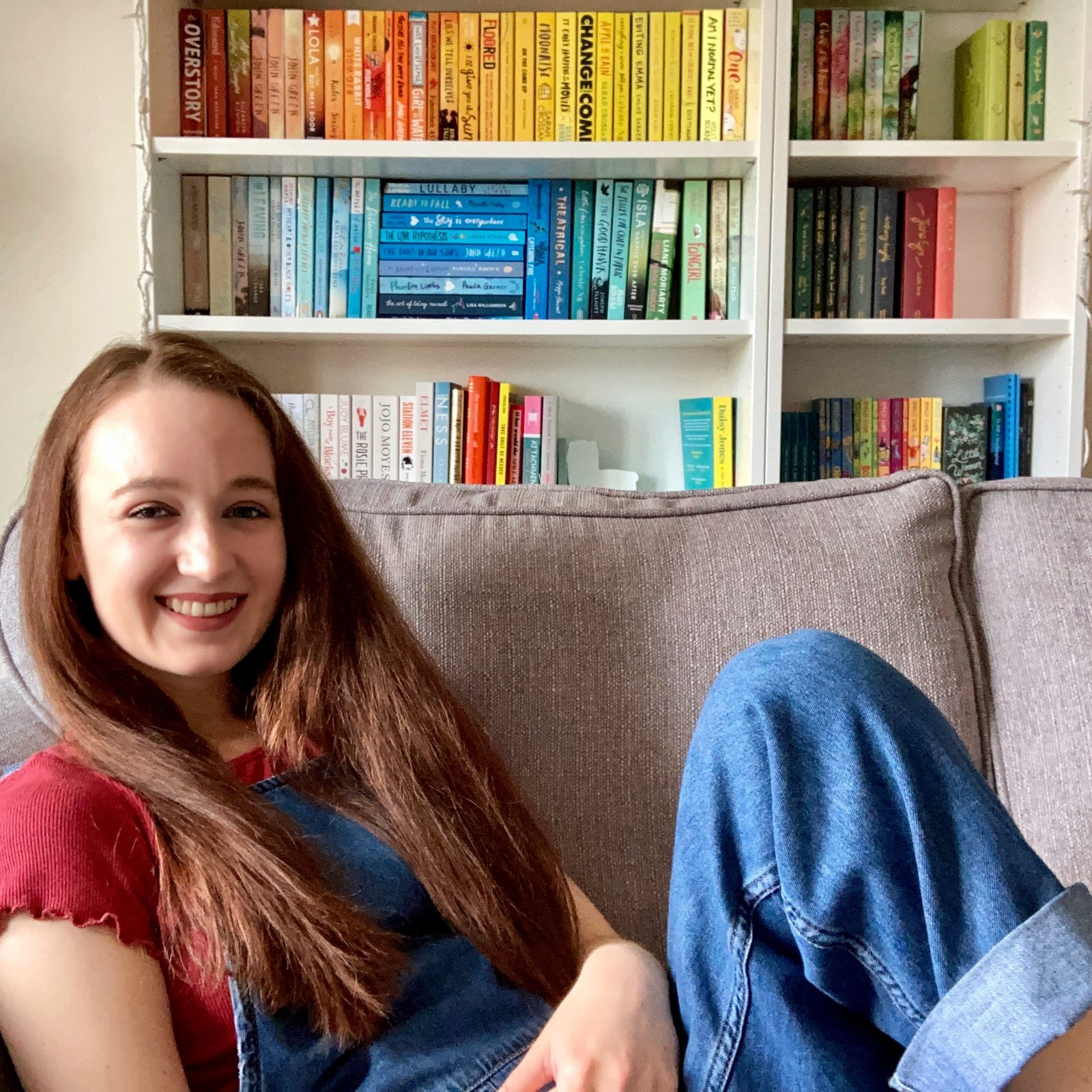 Pippa comfortably propped up on grey sofa, one leg bent up. Hair down, wearing red t-shirt and blue demin dungarees. Shelves of rainbow bookshelf (mostly blue and yellow) visible in background.