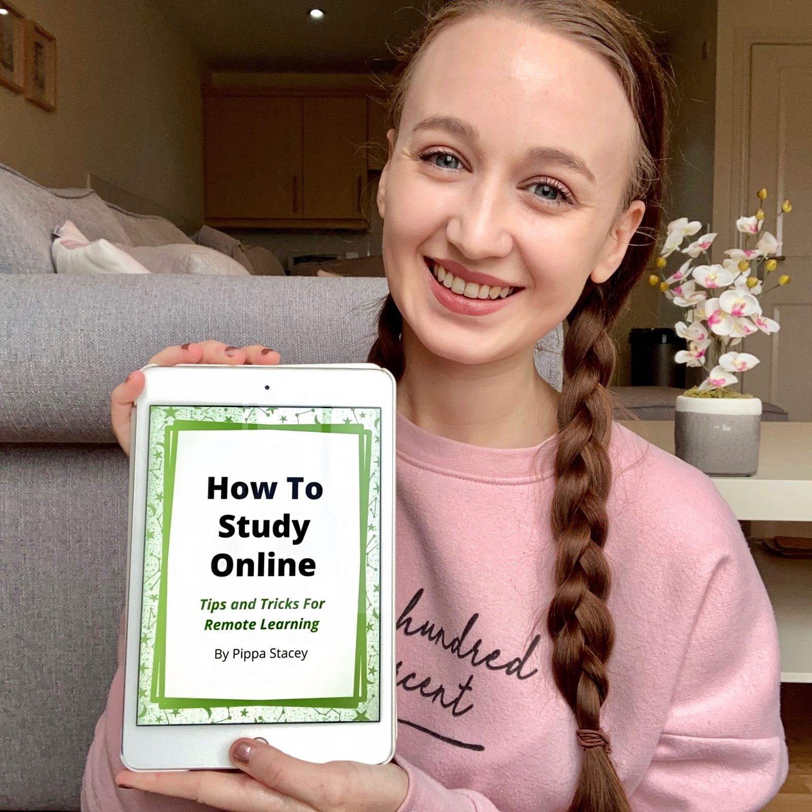 headshot of pippa, sat on floor wearing pink jumper and brown hair in twi plaits, holding up an iPad showing the front cover of 'how to study online' ebook
