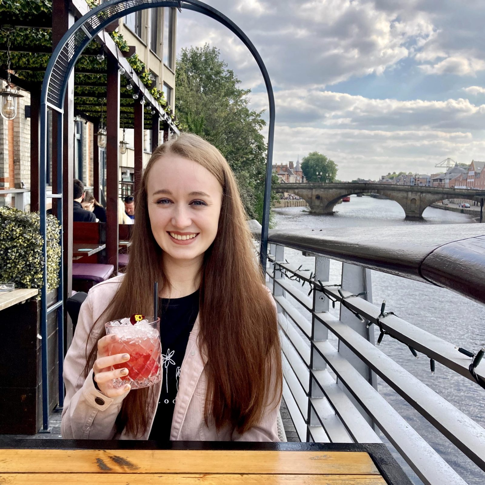 pippa sat at table outdoors with river visible in background. pippa is wearing a pink denim jacket with a black top under it, holding up a red 'mocktail' and smiling